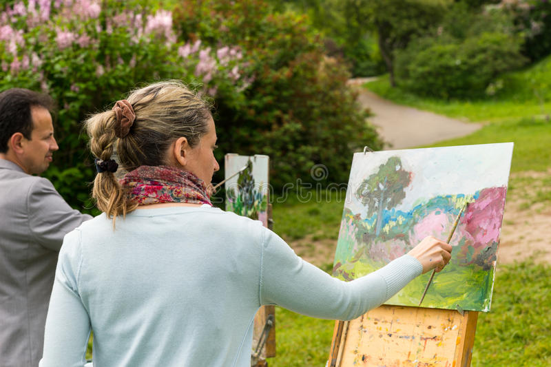 Two serious professional painters outdoors. Two serious professional painters standing in front of their easels and painting outdoors with background of royalty free stock photos