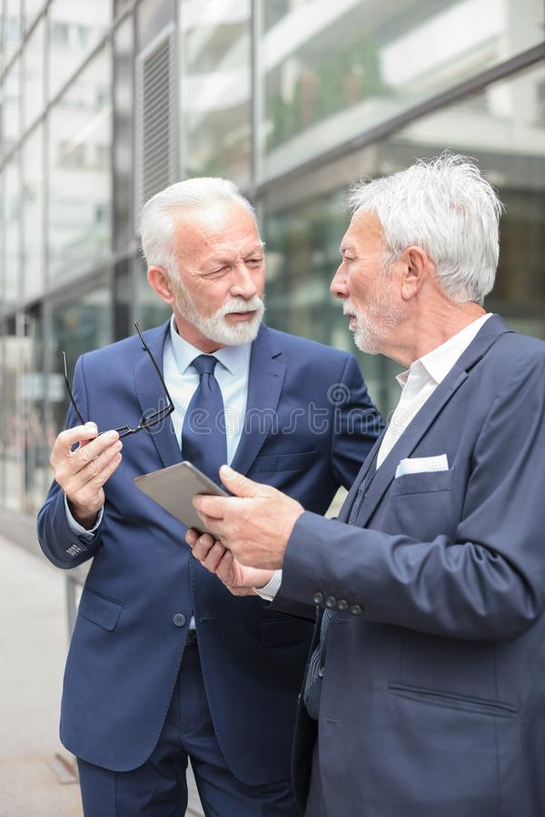 Two serious senior businessmen working on a tablet looking at each other and discussing royalty free stock image
