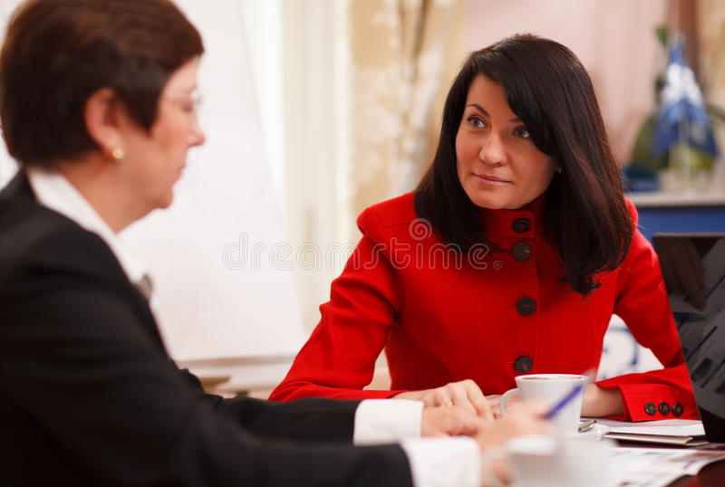 Two serious women in a business meeting. Sitting at a table in the office together analysing paperwork and putting together a business plan royalty free stock images