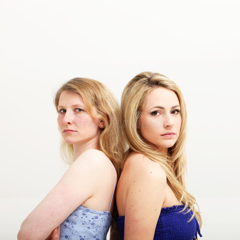 Two Serious Women Standing Back To Back Royalty Free Stock Photos