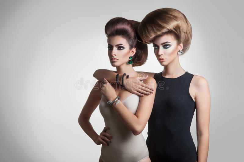 Two serious young girls with creative hairstyle looking away. In studio stock photos