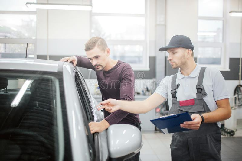 Two serious young men stand at car. Owner leans to it and looks inside of salon. Worker points with pen. He is royalty free stock photography