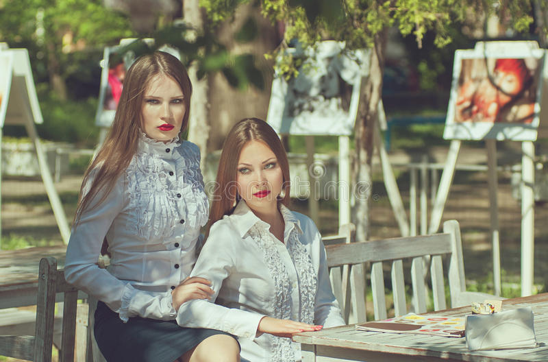 Two serious young women with long hair and red lips royalty free stock photos