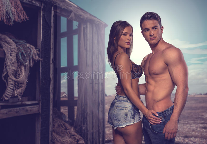 Two Couple Posing Beside Old Wooden House. Fashion Photo Shoot. Two Couple Posing Flaunting Perfect Body Beside Old Wooden House stock photography