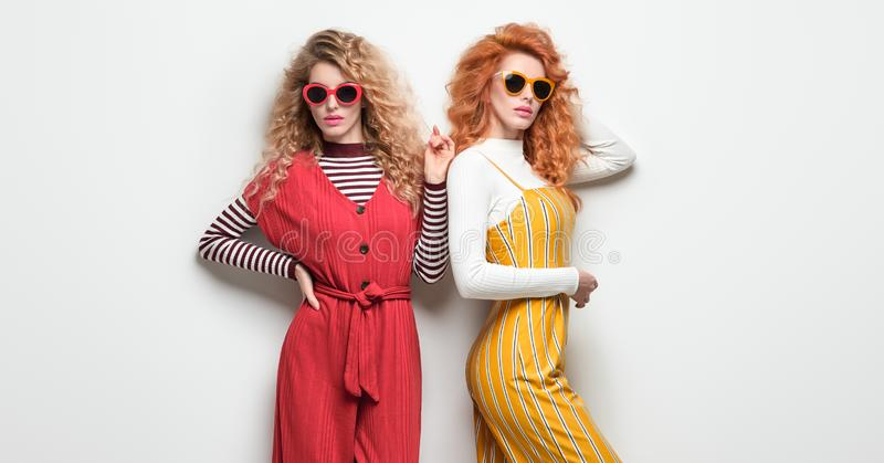 Two Gorgeous Girl in Fashion Outfit. Curly Hair royalty free stock photo