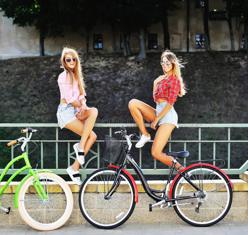 Two girls on a bicycles. Outdoor fashion portrait.  royalty free stock image