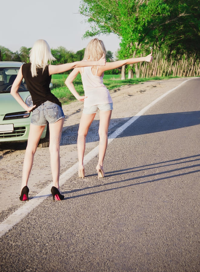 Two girls standing near car and hitchhiking. Road scene: two blonde girls standing near their broken car and hitchhiking. Rear view stock photos