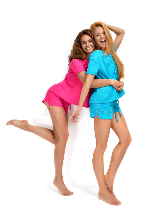 Two happy lady girls smiling laughing hugging in modern cas stock photos