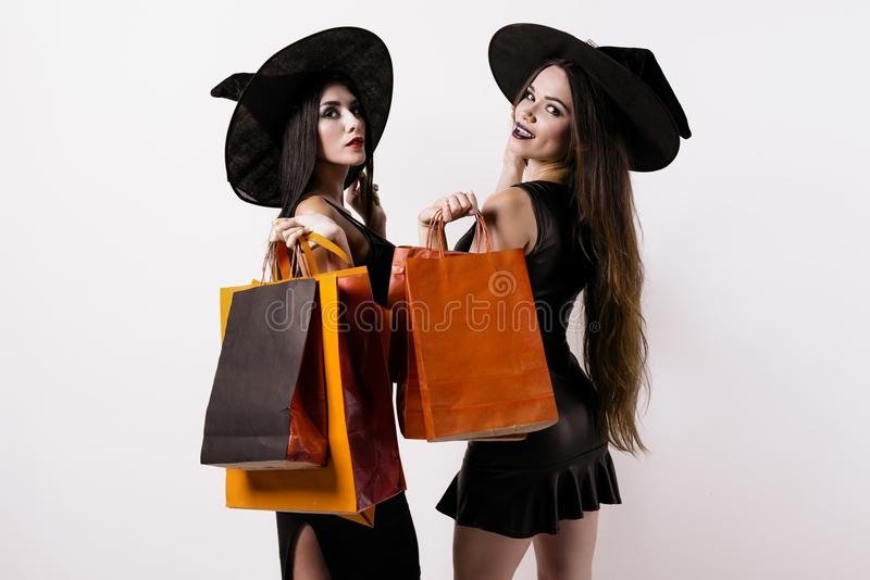 Two women in black dresses and witches hats posing with packages in hands. Two slender women in black dresses and wedges stand half a turn to the camera and are royalty free stock photography