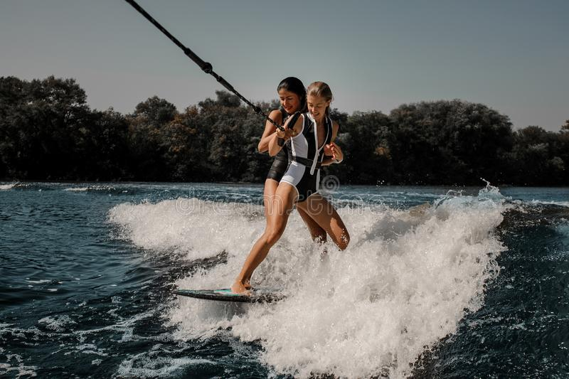 Two women wakesurfing on one board down the blue water. Two happy women wakesurfing on one board down the blue wave on hot sunny day royalty free stock image
