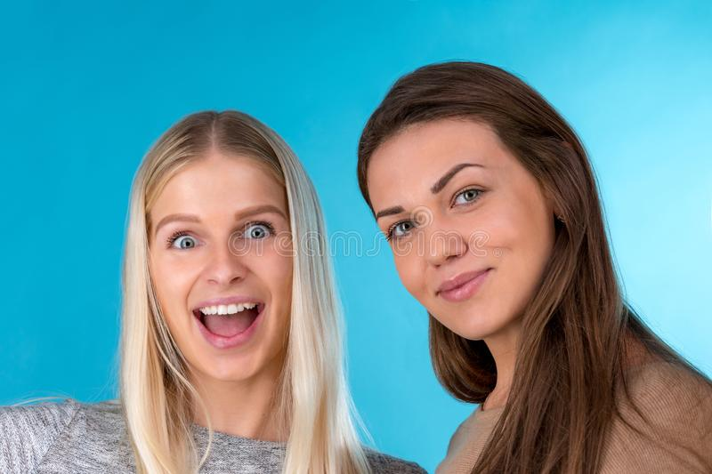 Two young beautiful slim women have a fun and posing in studio. Blonde girl and brunette girl on blue background. royalty free stock photography