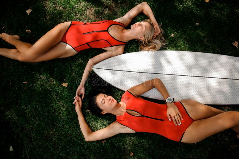 Two girls lying on the two sides of the wakeboard. Two young girls, blonde and brunette, in red swimsuits lying on the two sides of the white wakeboard on the royalty free stock image