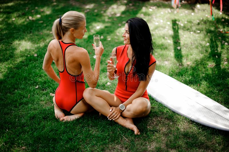 Two girls in sitting and drink champagne near the wakeboard. Two young girls, blonde and brunette, in red swimsuits sitting near the wakeboard on the green grass stock photos