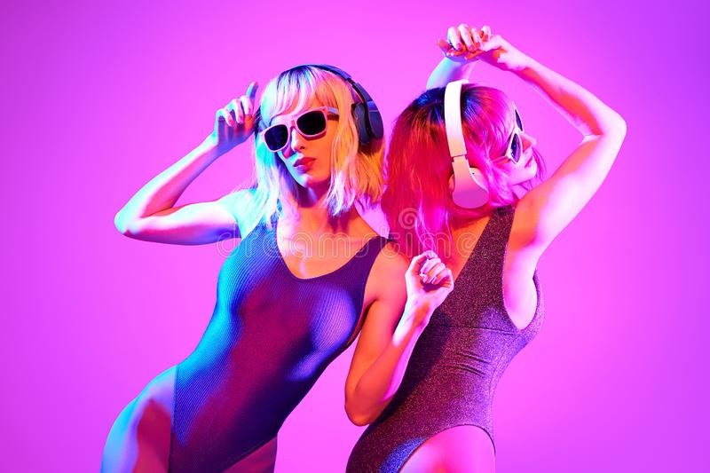 Two shapely DJ girl with Dyed Hair dance. Art neon. Two shapely fashionable DJ girl dance enjoy music in colorful neon uv purple blue light. Rave house music royalty free stock photography