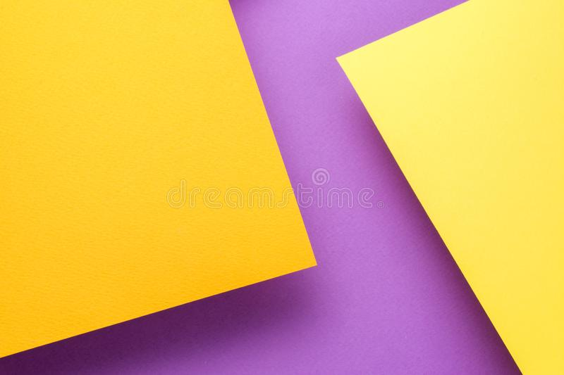 Two sheets of yellow and orange paper soar above the purple background. The sheets cast a shadow. royalty free stock images