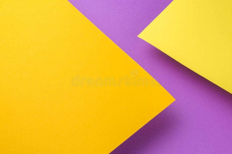 Two sheets of yellow and orange paper soar above the purple background. The sheets cast a shadow. royalty free stock photos