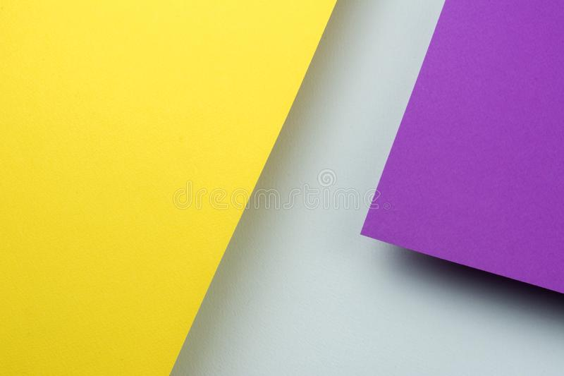 Two sheets of yellow and purple paper soar above the blue background. royalty free stock photos