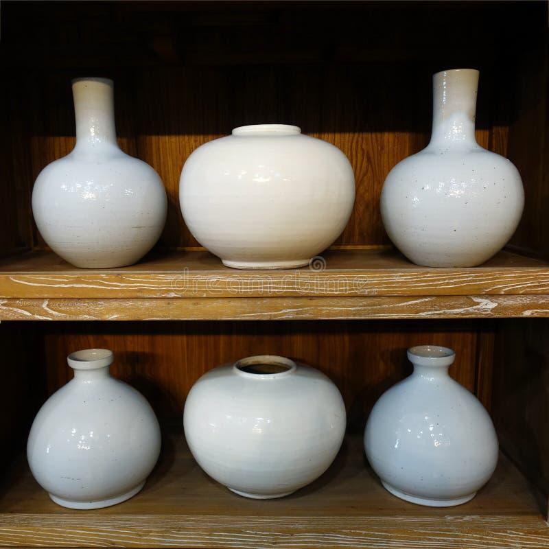 White Handmade Pottery - Six Vases. Two Shelves of White Handmade Pottery - Six Vases stock photography