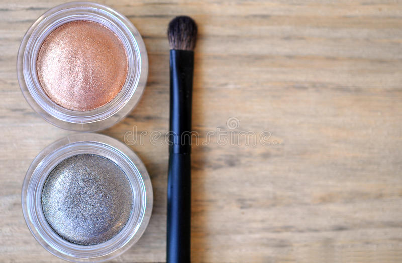 Two shimmer eyeshadow glass boxes and brush on wood table. Background royalty free stock images
