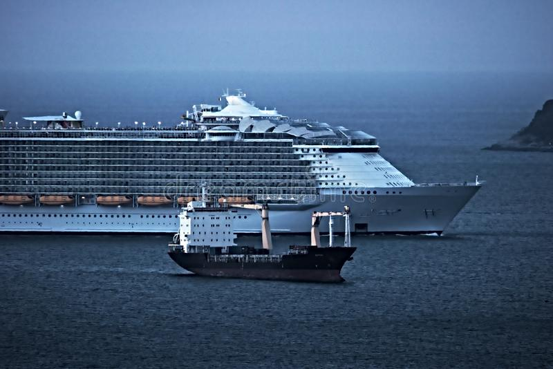 A cruise ship in comparison with a merchant ship. Gulf of La Spezia. Italy stock images