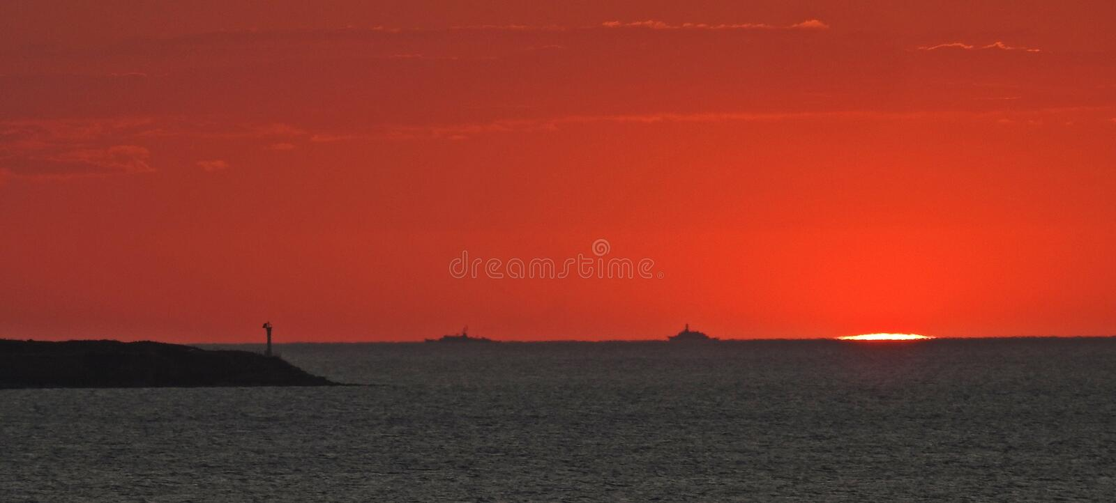 Ships on the horizon. Two ships on the horizon, lighthouse and the setting sun, sunset colors, clouds and sun stock photos