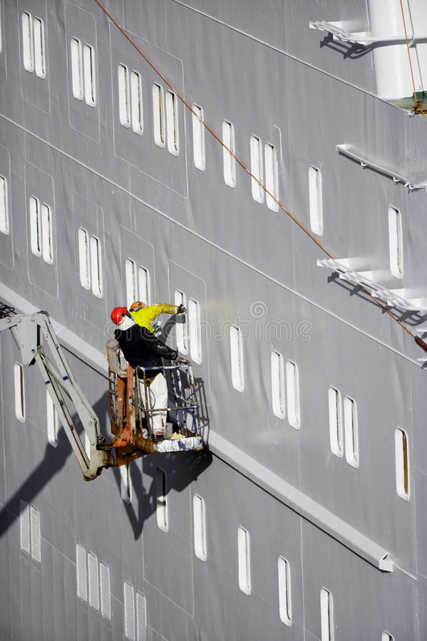 Two shipyard workers on cherry picker royalty free stock image
