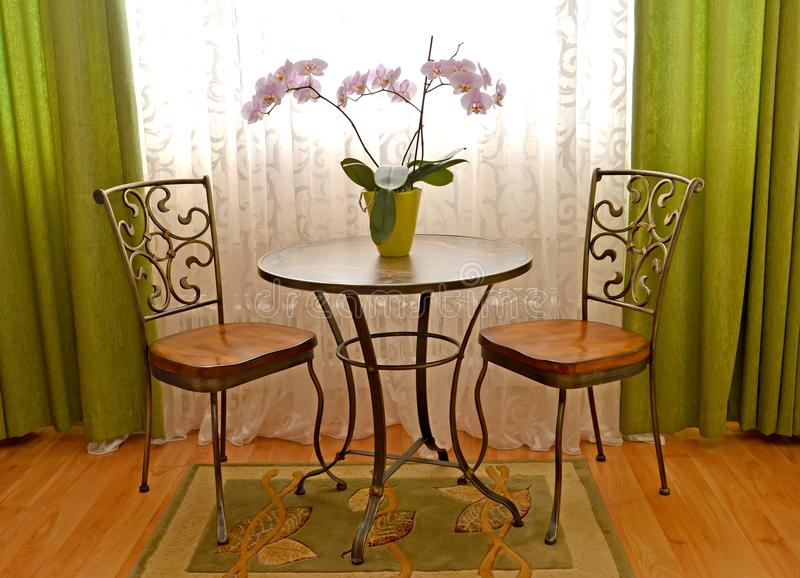 Two shod chairs and little table about a window of a modern classical drawing room.  stock photos