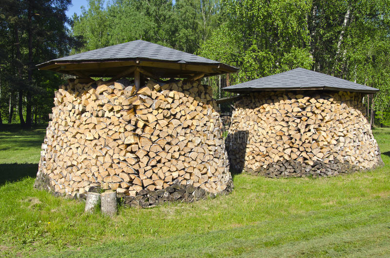 Two shopped firewood stacks. In summer park stock images