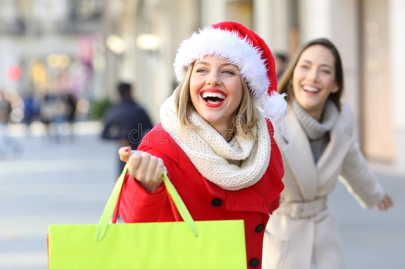 Two shoppers shopping running on the street. Two shoppers shopping holding bags running searching shops outdoors on the street stock images