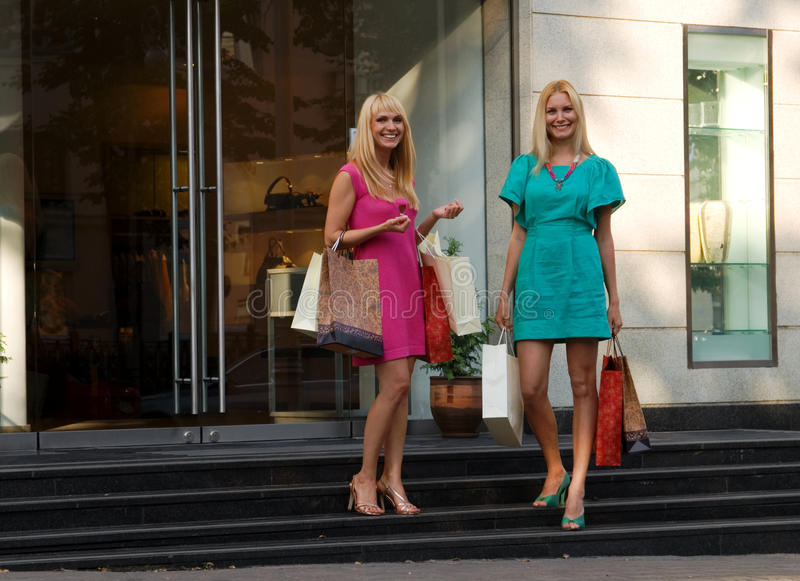 Two shopping girl friends stock photos