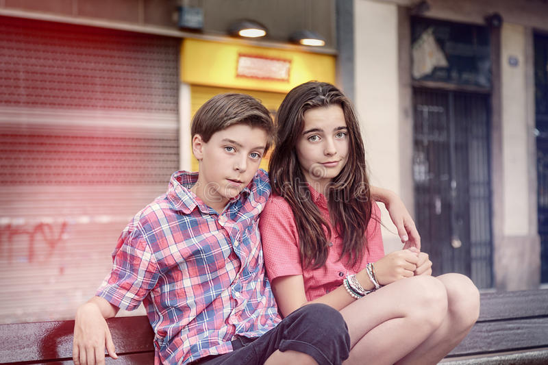 Two siblings crouching on a bench. Toned image of two siblings crouching on a bench royalty free stock image