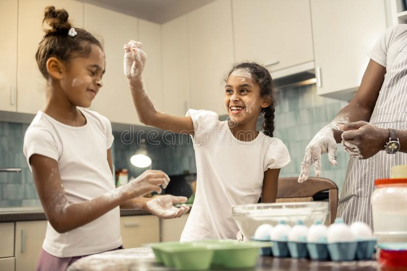 Two siblings feeling funny and excited while cooking together. Two siblings. Two beautiful funny siblings feeling funny and excited while cooking together royalty free stock photo
