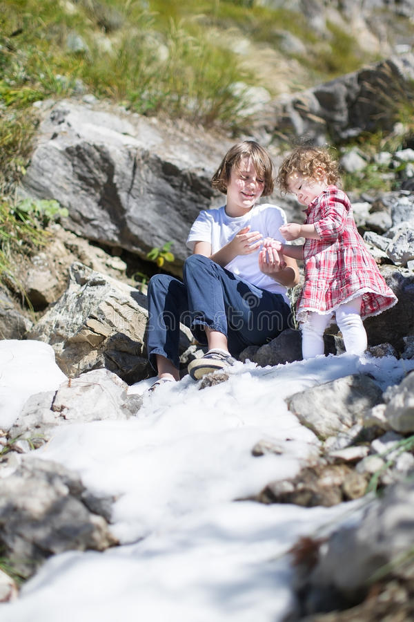 Two Siblings Playing With Snow In Mountains Stock Photo