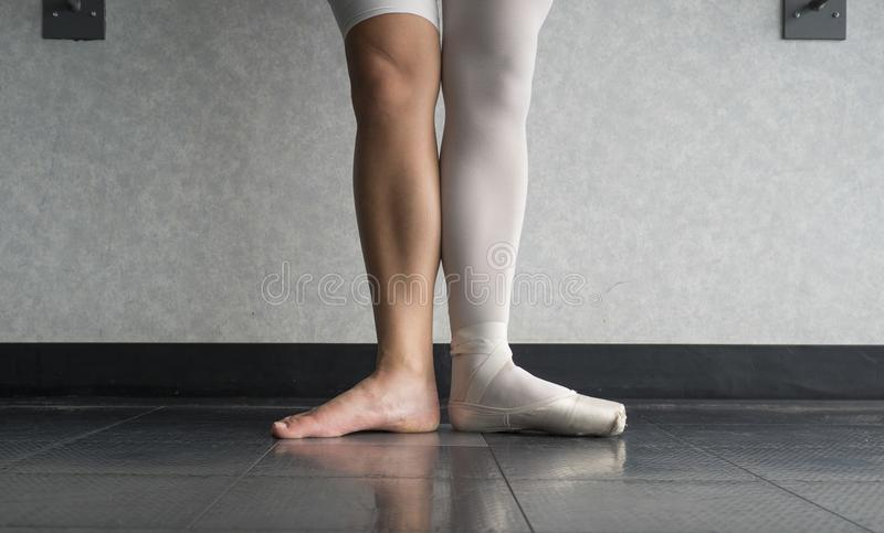 Two sides to a ballerina, one leg wearing her ballet slipper pointe shoe on one foot, and one leg bare. In the dance studio royalty free stock image