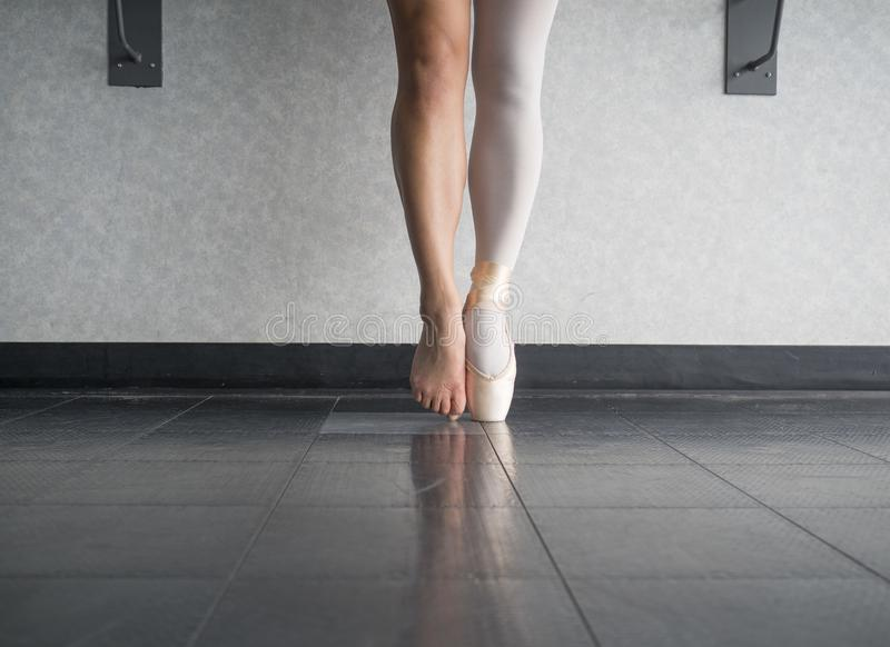 Two sides to a ballerina`s feet, both in and out of her dancing ballet shoes. In a studio setting stock photography