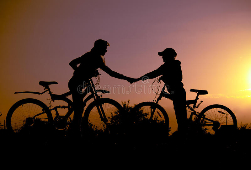 Two silhouette with bicycles at sunset. Heart stock photos