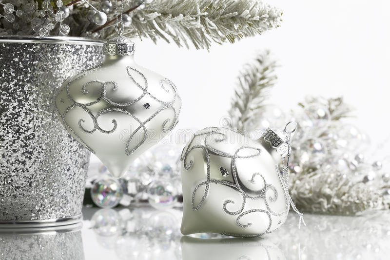 Two Silver Christmas Ornaments. Two Ivory and silver colored Christmas ornaments, one hanging on flocked pine branch the other lying on white reflective surface royalty free stock photos