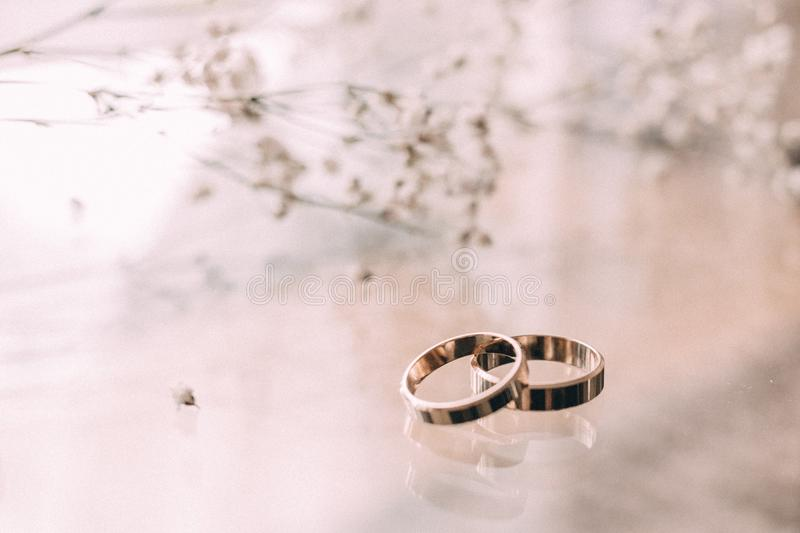 Two Silver-colored Rings on Beige Surface royalty free stock image