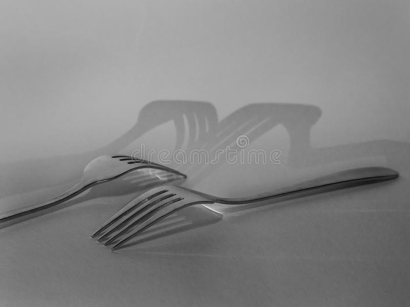 Two silver forks cast a shadow on grey background royalty free stock photography
