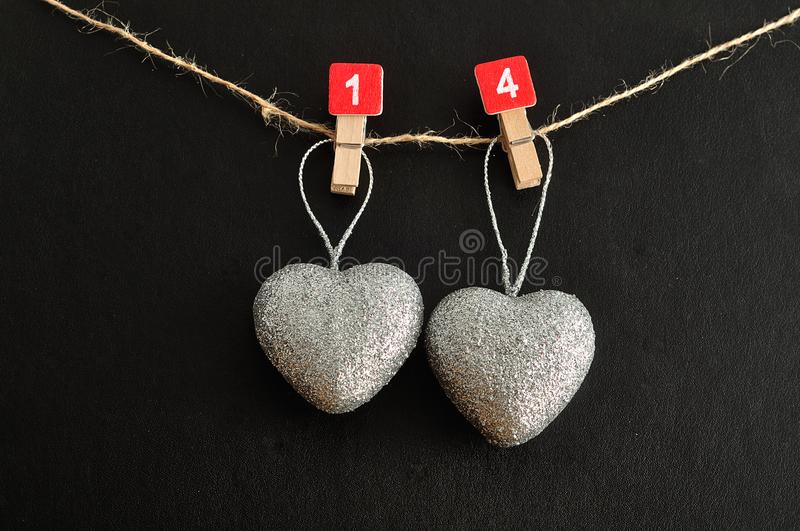 Two silver hearts hanging on a rope royalty free stock photos