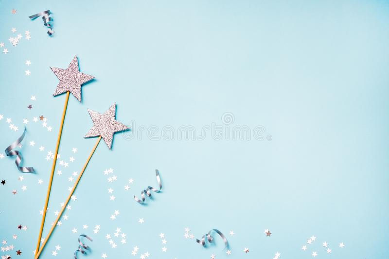 Two silver party magic wands, sequins and ribbons on a blue background. Copy space. Two silver party magic wands, sequins and ribbons on a blue background. Copy stock photography