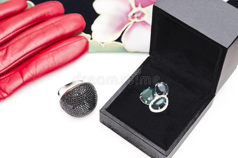 Two silver rings, a black box, a red glove and a scarf. Two silver rings, black box, a red glove and a scarf stock photo