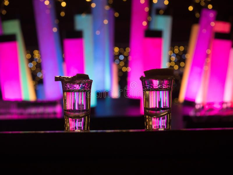 Two silver tequila shots with lime on bar counter with color changing  led tube lamps. Closeup view stock photos