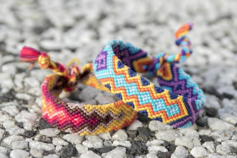 Two simple handmade homemade natural woven bracelets of friendship on stone background. Rainbow colors, checkered pattern stock photos