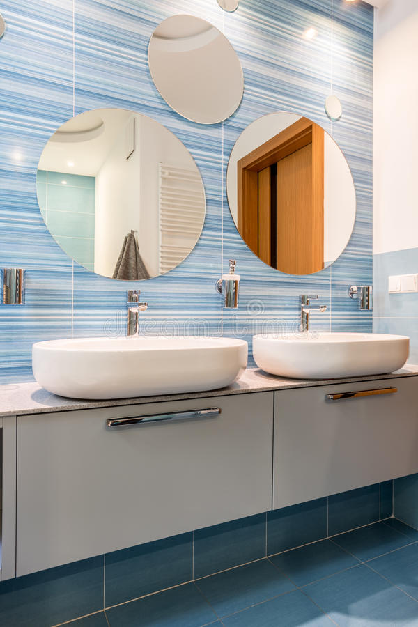 Two sinks in blue bathroom. Two sinks on white simple cupboards in modern blue bathroom with round mirrors royalty free stock images