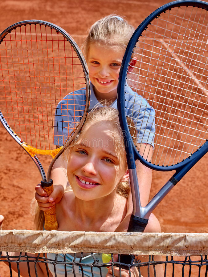 Two sister girl athlete with racket and ball. On brown tennis court royalty free stock photo