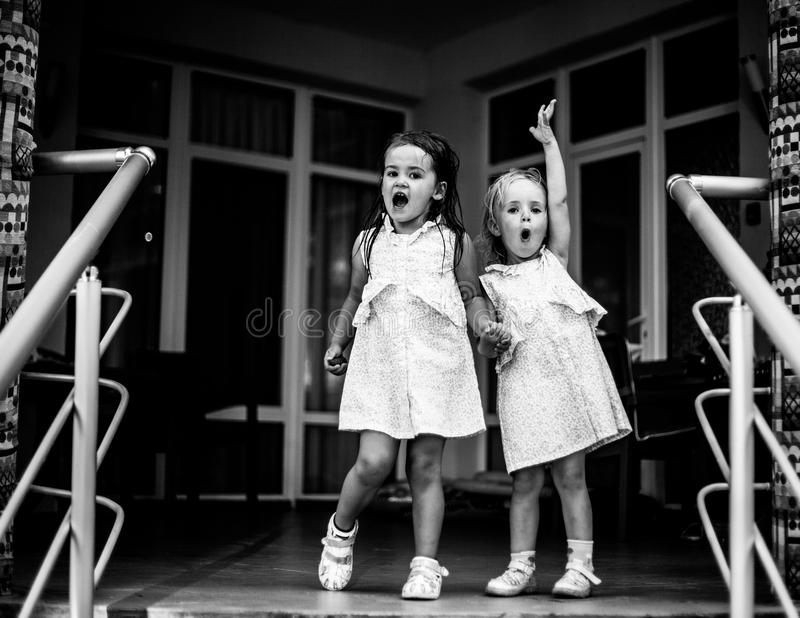 Two sisters baby girls in the same dresses, holding hands. Black and white photo. Small sweet sisters, dressed the same dresses, holding hands, having fun, happy royalty free stock photo