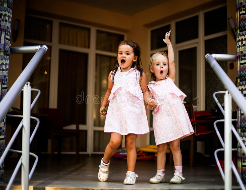 Two sisters baby girls in the same dresses, holding hands. royalty free stock photography