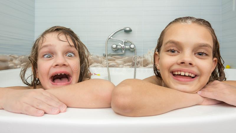 Two sisters bathe in the bath and make fun faces royalty free stock photo