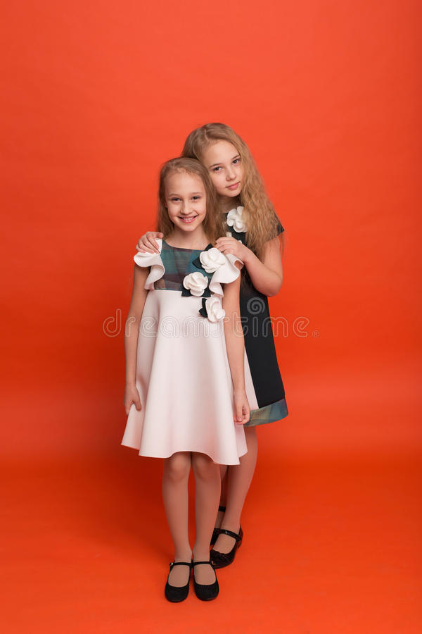 Two sisters in beautiful stylized dresses on a red background in stock photos